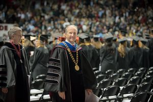 Dr. Bell during Commencement smiling for the camera as he leaves the graduation floor