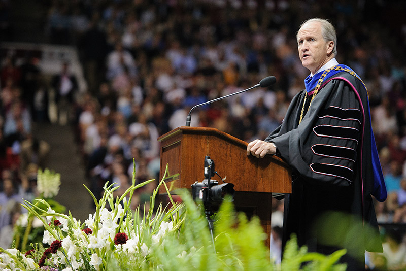 Dr. Bell at the podium during Commencement