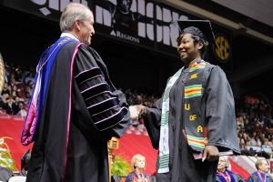 Dr. Bell shakes a female graduate with short hair's hand at 2017's Spring Commencement