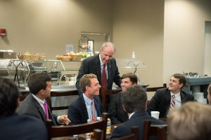 Dr. Bell talks to students in suits who are seated at a long table