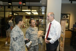 Dr. Bell talks with two African-American students in army uniform.