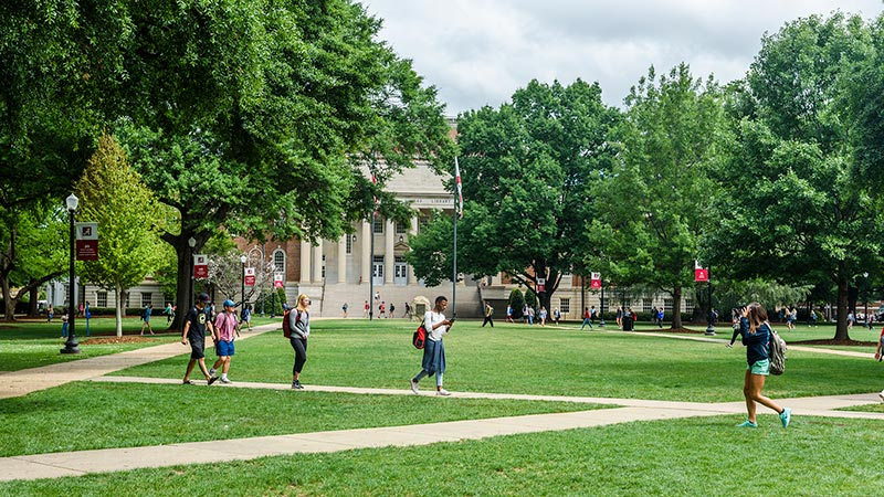 A view of the Quad and Gorgas Library with students walking