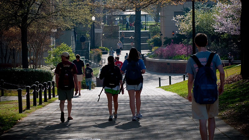 Students walking down a path outside near the business school