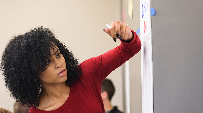 A student works out an idea on a marker board.